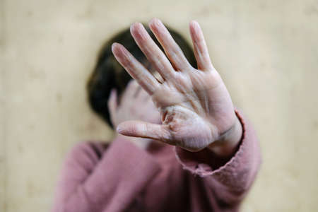 Woman raised her hand to protect her face. The concept of a violence against women