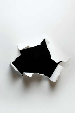 Ripped hole in white paper with black background inside 免版税图像