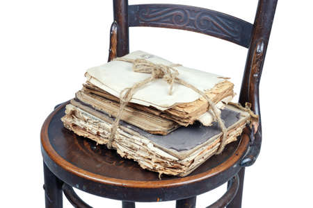 Old books and papers tied with a rope on a vintage wooden brown chair, isolated on a white background
