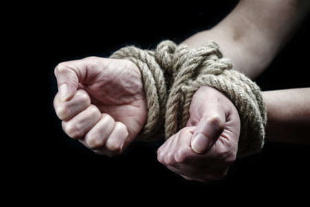 Hands of a victim woman tied up with rough rope on the black background. Stop abusing violence concept Foto de archivo