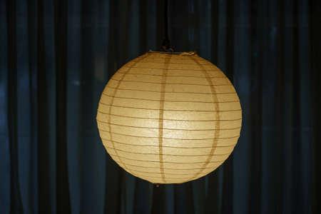 Yellow paper illuminated chandelier in dark interior 免版税图像