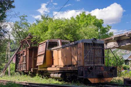 Old rusty diesel locomotive with broken wooden cargo wagon on railway
