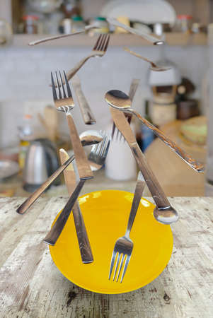 Spoons, forks and red plate flying over the vintage wooden table with blurred kitchen background Stock fotó