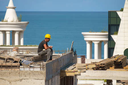 Batumi, Georgia, September 22, 2020: Building worker during a brake on the top of the construction site, blue sea and sky background