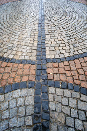 Traditional color stone pavement in perspective after the rain. Abstract background of old cobblestone pavement, soft focus