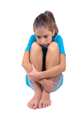A sad and upset girl in blue shirt with hands wrapped around her knees sitting on the floor