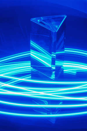Glass Prism with reflection on a abstract blue neon stripey background