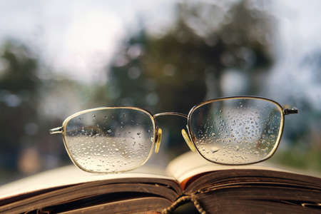 Glasses and open book on the window sill, selective focus Banque d'images