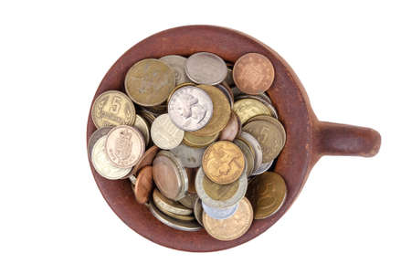 Top view of a clay brown pot full of various money coins, isolated on a white background Banque d'images