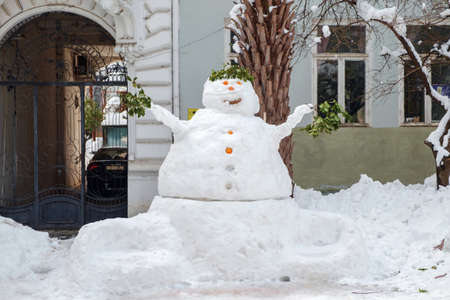 A winter street scene with snowman decorated with tree branch and citruses Banque d'images - 158672252