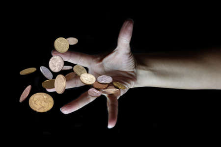 Hand throwing various money coins on blurred dark background, selective focus