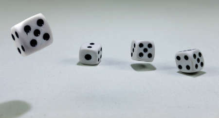 White playing dice cubes in motion on the white canvass surface Banque d'images