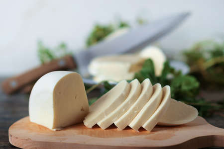 Sliced cheese on a wooden board with green herbs background. Georgian cheese sulguni, selective focus