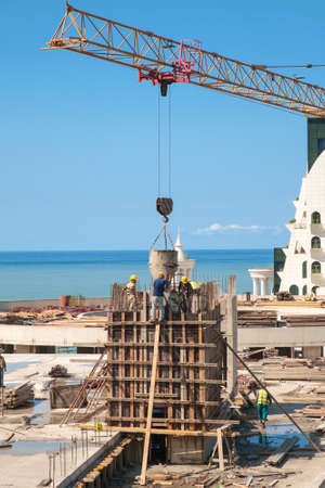 Building worker pouring concrete on the top of the construction site with blue sea background
