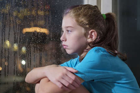 A brown eyed girl in blue shirt sitting on the window sill behind a foggy window with blurred night background