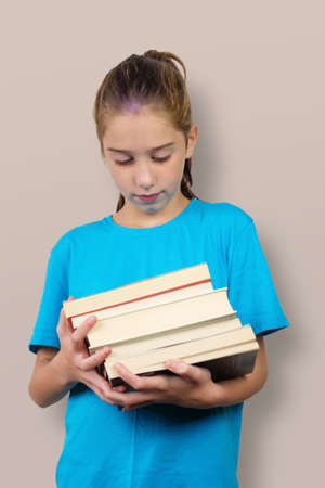 A little girl holds stack of school books Banque d'images - 159029677