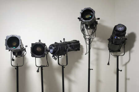 Theater stage equipment, black spotlight projectors standing behind a white wall