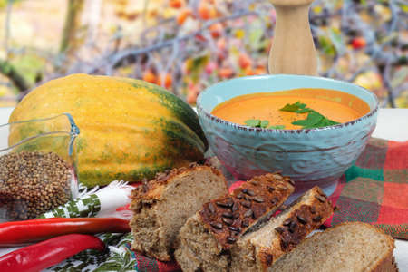 Pumpkin soup on the table with white tablecloth at the autumn garden