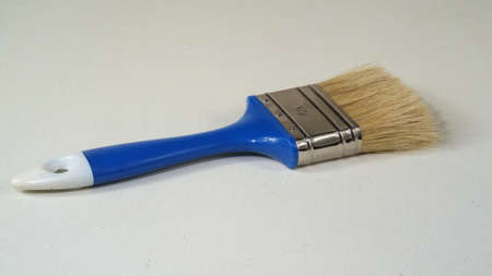 Paint brush with blue wooden handle and synthetic hairs on white canvass surface