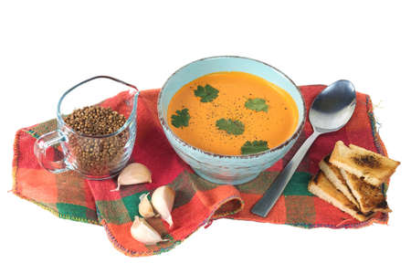 Pumpkin soup with croutons and onions on the colorful plaid tablecloth isolated on a white background,