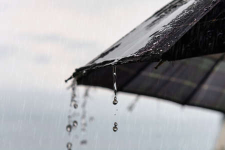 Rain drops pouring from a umbrella, rainy weather concept, selective focus