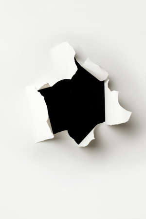 Ripped hole in white paper with black background inside Banque d'images - 159136377
