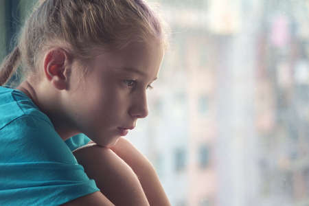 A brown eyed sad girl sitting on the window sill  with blurred outdoor background Banque d'images - 159140904