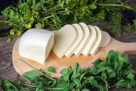 Sliced cheese on a wooden board with green herbs background. Georgian cheese sulguni Banque d'images - 159141343