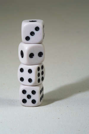 Stack of the white playing dice cubes on the white canvass surface
