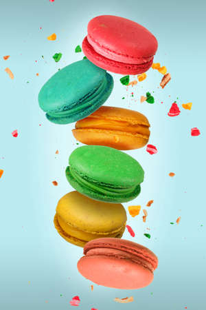 Colorful French macaroons falling or flying in motion on a light blue background