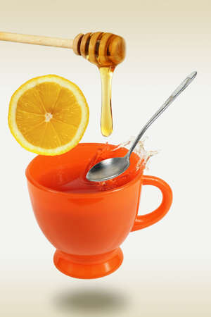 Honey dripping ln the flaying orange teacup with spoon and lemon