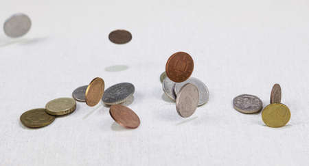 Different countries coins falling down on the white canvass surface. Coins levitating in the air