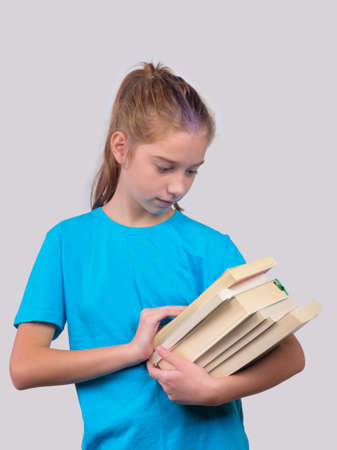 A little girl in blue shirt holds stack of school books Banque d'images