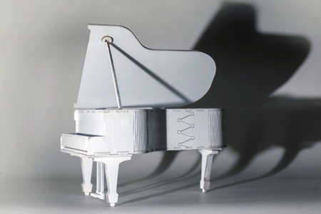 Decorative toy white grand piano illuminated by sharp light Imagens