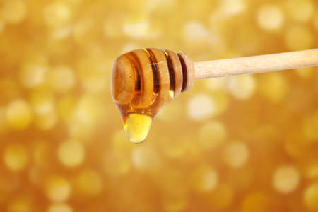 Honey dripping from wooden honey dipper with golden abstract lights blurred background