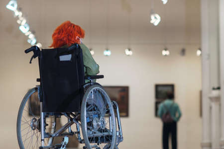 Disabled girl with red hair in a wheelchair visiting the art gallery, selective focus Banque d'images