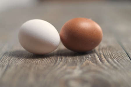 White egg and brown egg on the wooden table, selective focus