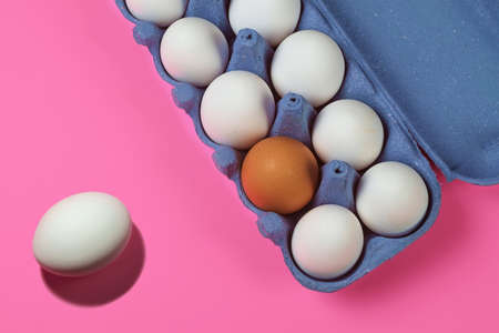 Brown egg between white eggs in a paper tray on a pink surface