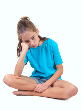 A sad and upset girl in blue shirt sitting on the floor