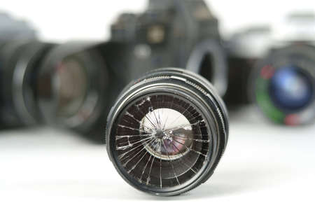 broken camera lens with blurred photography equipment background, selective focus
