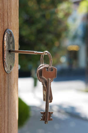 Set of keys on the ring in the keyhole with blurred street background, selective focus