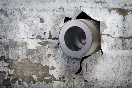 Concept of paparazzi or hidden camera, camera lens looks out through a hole in broken grunge wall