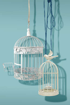 Two vintage white empty bird cages on a light blue background