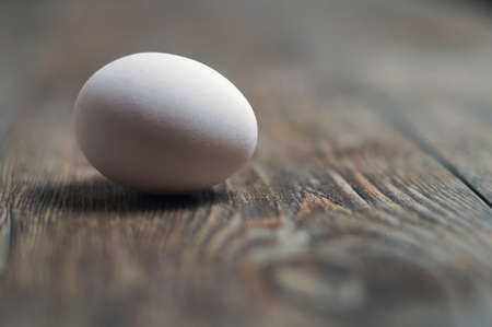 White egg on the wooden table, selective focus