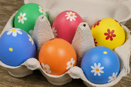 Colorful painted Easter eggs  in a paper tray on a wooden table