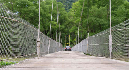 A black car is crossing hanging bridge with wooden planks over the river
