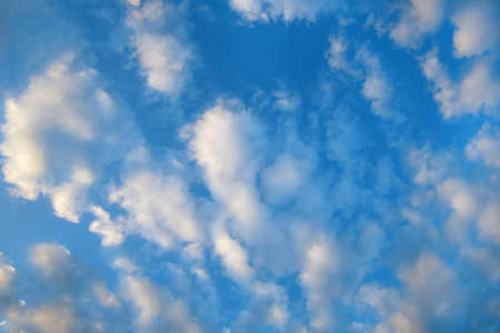Blue sky background, white fluffy clouds lit by sunset light. Banque d'images