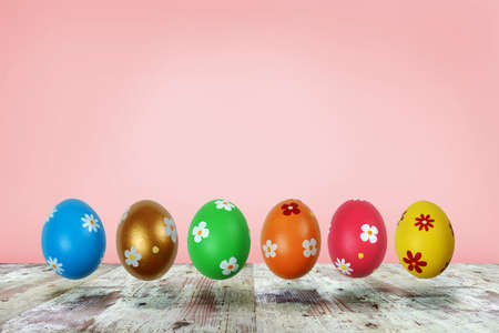 Colorful painted Easter eggs levitating over white wooden table surface