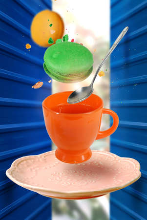 Color macaroons and silver spoon falling in to levitating orange teacup with tea, blurred background