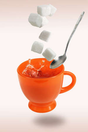 Levitating orange teacup flying spoon and sugar cubes
